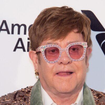 Elton John wears a colorful blazer and sunglasses