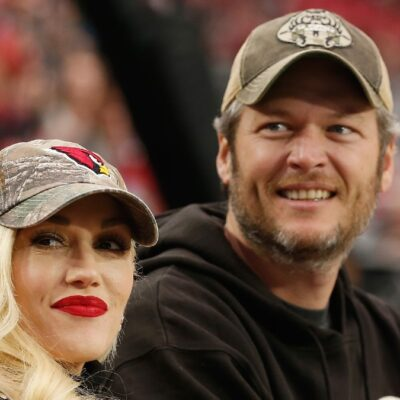 Gwen Stefani wears a brown hat and sits with Blake Shelton, also in a brown hat