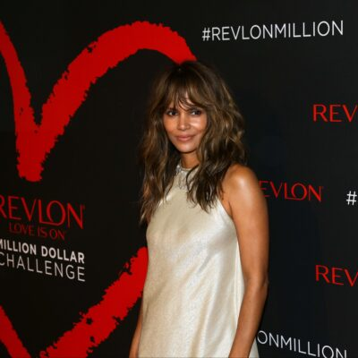 Halle Berry wears an ivory sheath dress as she stands in front of a black and red background