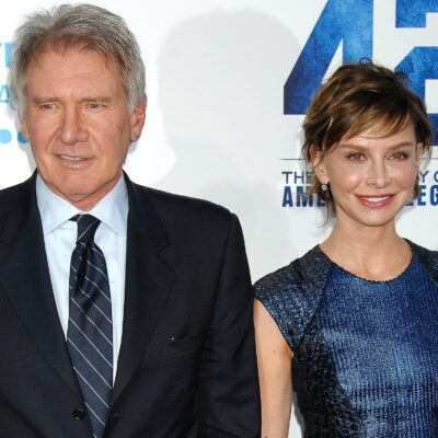 Harrison Ford on the left, together with Calista Flockhart, holding hands at a red carpet event.