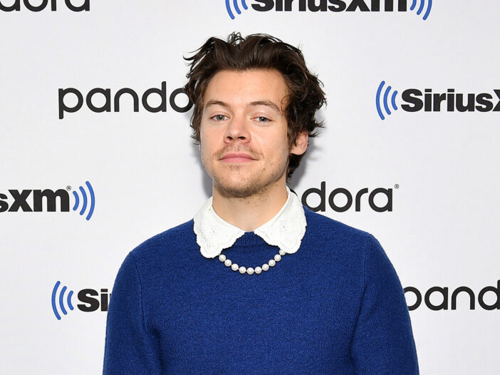 Harry Styles wearing a blue sweater with a frilly collar and a pearl necklace