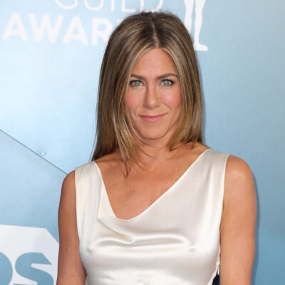 Jennifer Aniston in a white dress looking at the camera