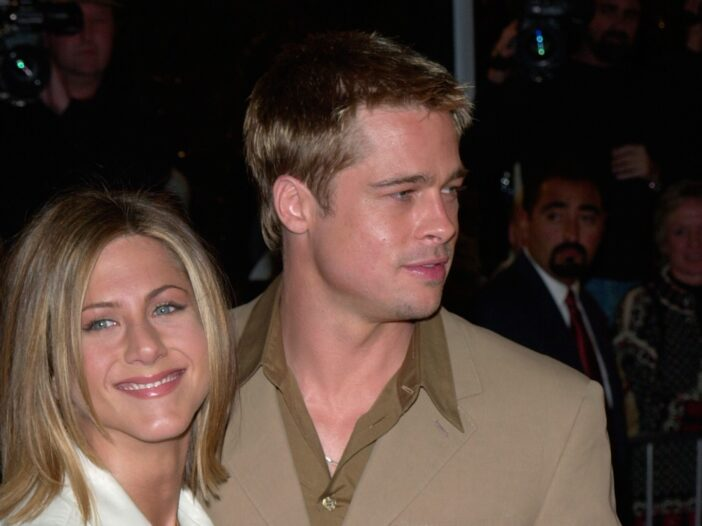 Jennifer Aniston in a white coats stands with Brad Pitt, wearing a beige coat, on the red carpet