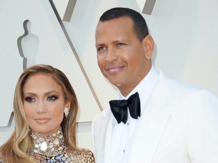 Jennifer Lopez smiling in a silver dress with Alex Rodriguez in a white tux