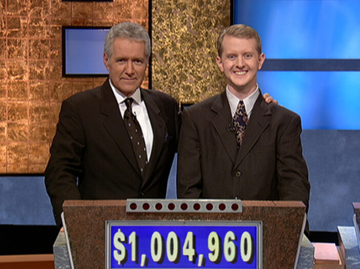 Alex Trebeck on the left, standing with Ken Jennings on the set of Jeopardy!