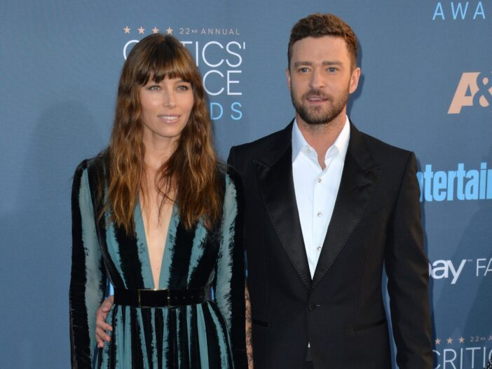 Jessica Biel, in a green and black dress, stands with Justin Timberlake, wearing a black suit