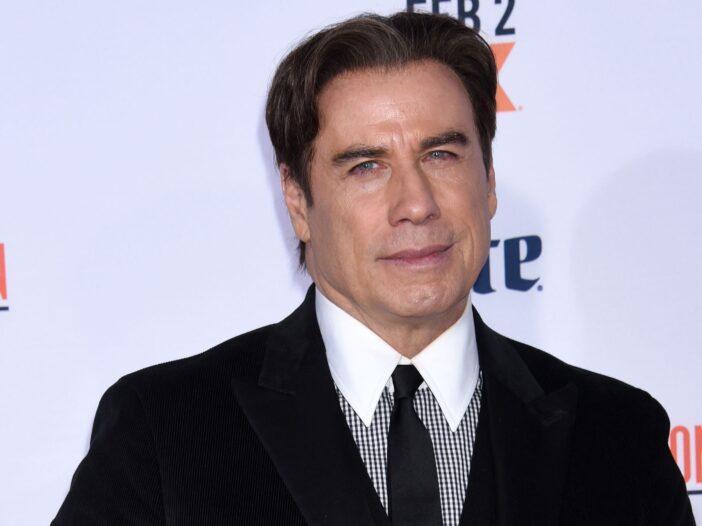 John Travolta wears a black suit while attending a movie premier.