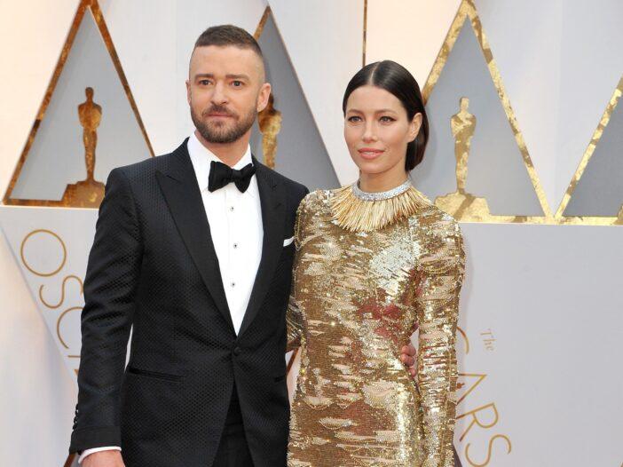 Justin Timberlake (right) in a tux with Jessica Biel in a gold dress on the red carpet at the Oscars.