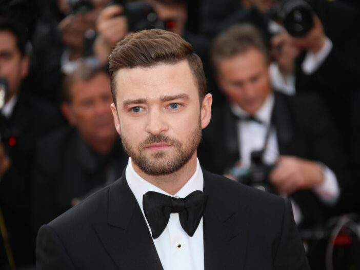 Justin Timberlake stands before photographers wearing a black tux on the red carpet