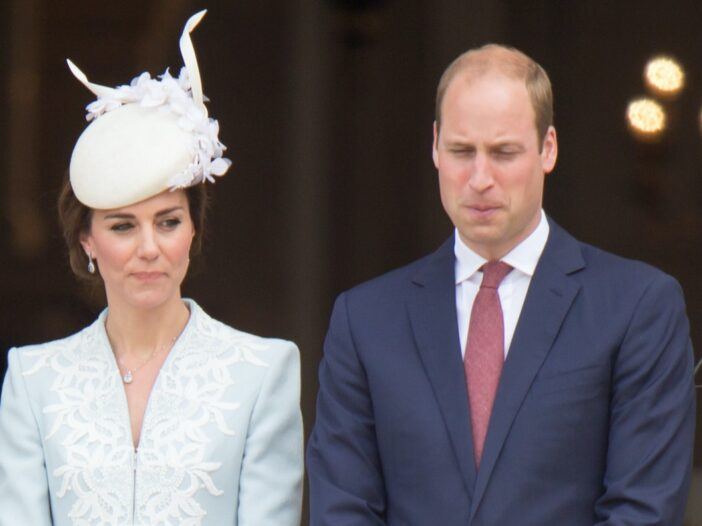 Kate Middleton in a light blue outfit with Prince William in a dark blue suit