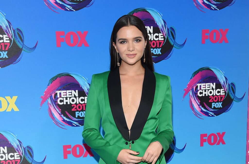 Katie Stevens in a satin emerald green suit jacket and locks sleek and straight at the Teen Choice Awards.