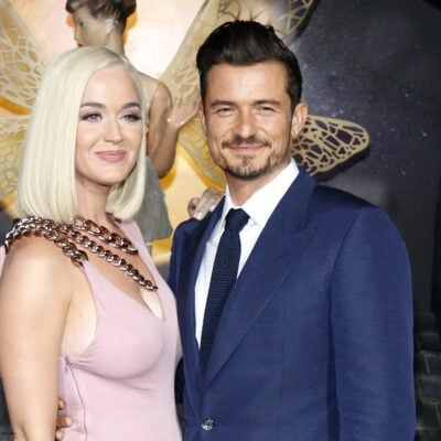 Katy Perry on the left in a pink dress, Orlando Bloom in a suit, standing with her.