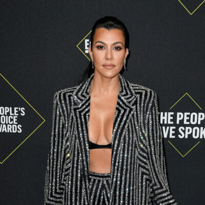 Kourtney Kardashian wearing a jacket, opened to reveal a skimpy bra