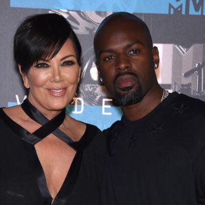 Kris Jenner and Corey Gamble, both dressed in black, walk the red carpet