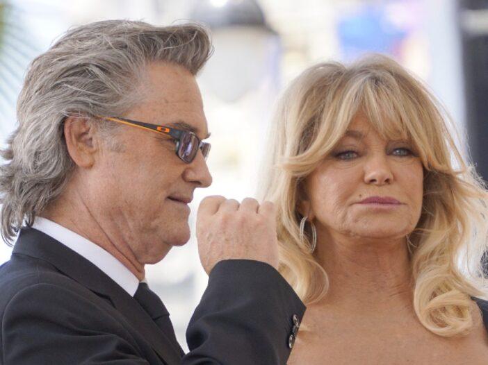 Kurt Russell raises a hand as he stands beside Goldie Hawn