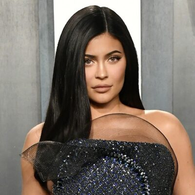 Kylie Jenner in a glittery halter top dress at a red carpet event.