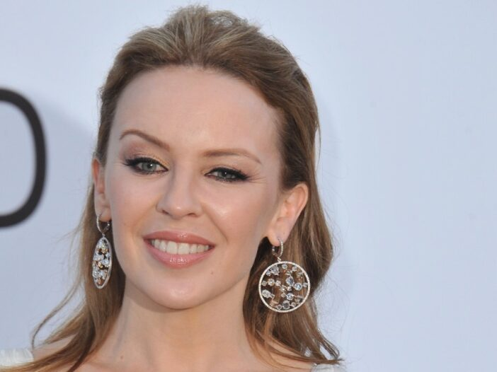 Kylie Minogue wears a white dress and smiles against a white background