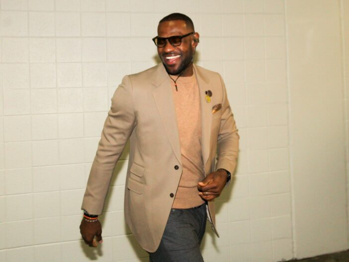 LeBron James wears a tan shirt and suit jacket as he walks into a basketball arena