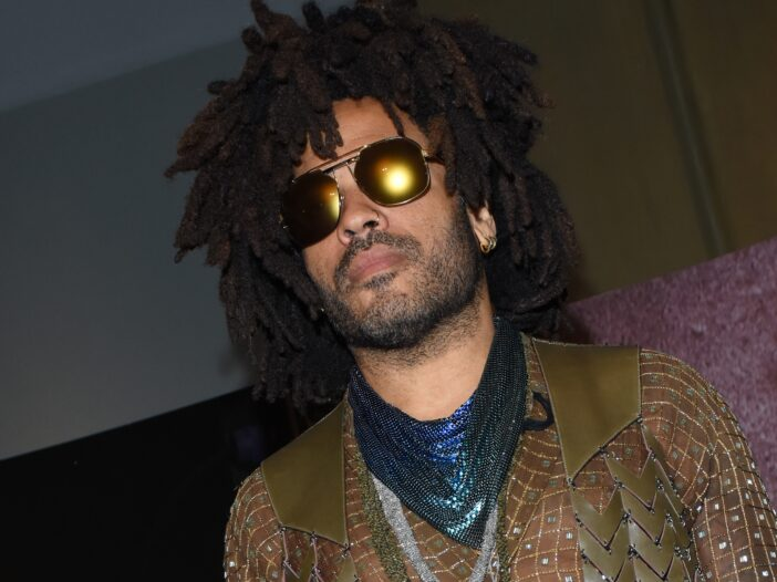 Lenny Kravitz wears a sheer shirt under a brown vest and blue scarf