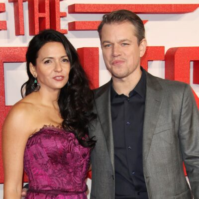 Luciana Barroso on the left in a pink dress, standing with Matt Damon in a suit.
