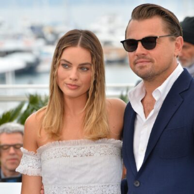 Margot Robbie wears an off-the-shoulder dress and stands with Leonardo DiCaprio, in a blue suit