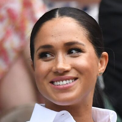Meghan Markle wears a white shirt and looks to the side