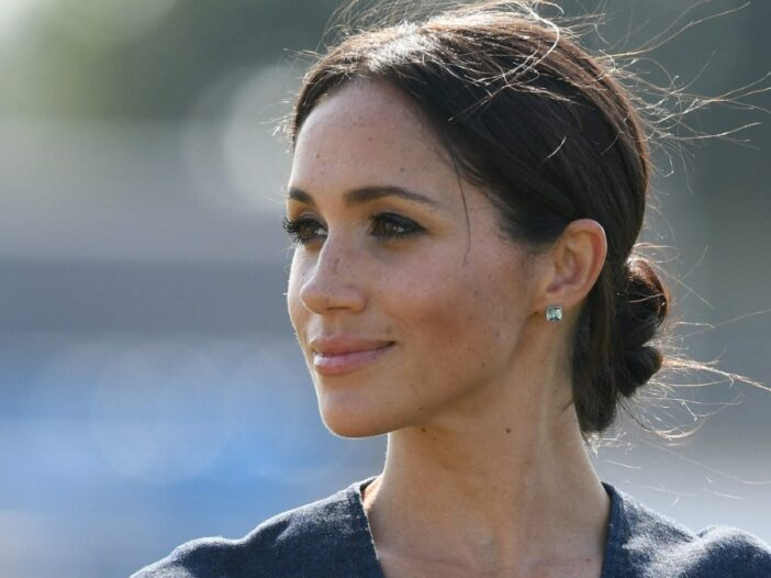 Meghan Markle wears a dark dress and looks off to the side, presenting her profile