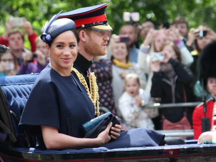 Meghan Markle smiles in a blue dress in a carriage with husband Prince Harry