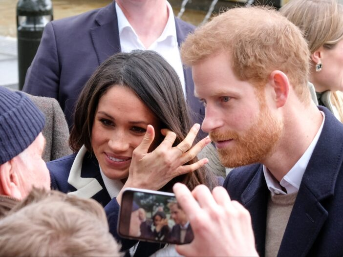 Meghan Markle smiles while standing with Prince Harry among a throng of supporters