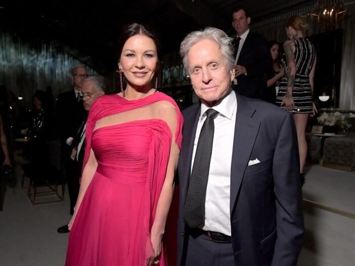 Catherine Zeta-Jones in a red dress, standing with Michael Douglas in a suit.