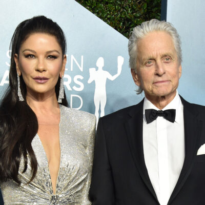 Catherine Zeta-Jones looking serious in a silver dress, standing next to Michael Douglas in a tux.