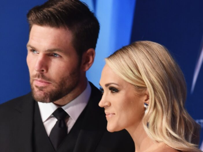 Mike Fisher, in a dark suit, stands with Carrie Underwood, in a blue dress