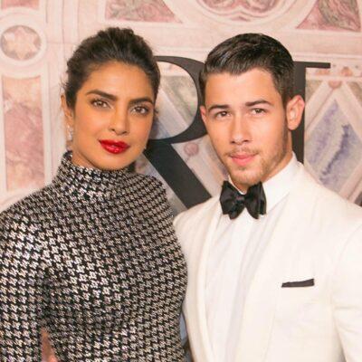 Nick Jonas in a white tuxedo with wife Priyanka Chopra in a silver dress