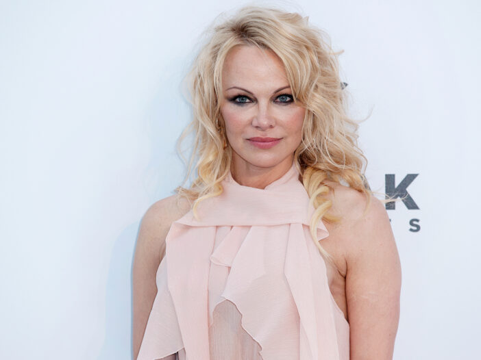 Pamela Anderson in a pink dress, standing in front of a white background.
