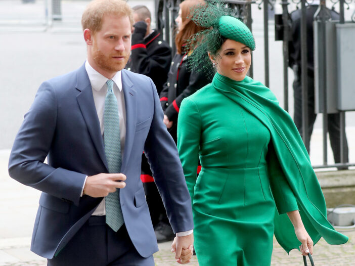 Prince Harry in a suit, holding hands with Meghan Markle, wearing a green dress.