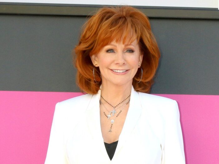 Reba McEntire smiling in a white jacket and black camisole