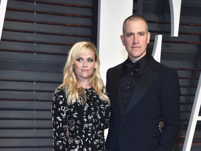 Reese Witherspoon in a black and white print dress and Jim Toth in all black tux at the Vanity Fair Oscar Party.