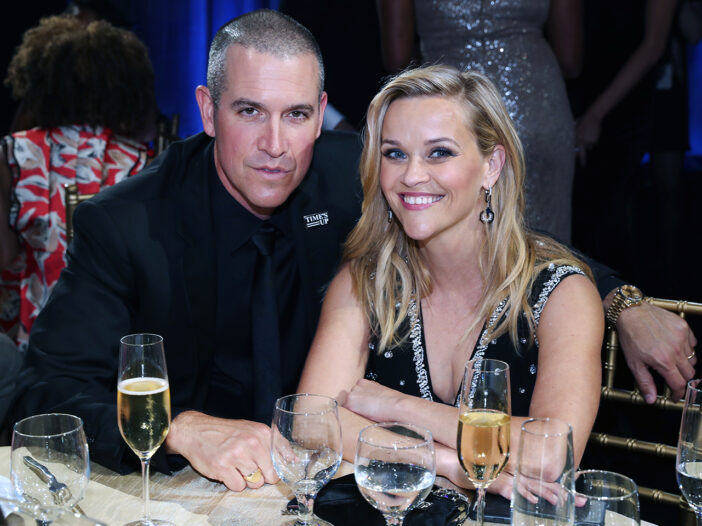 Jim Toth (right) and Reese Witherspoon sitting at a dinner table at a party.