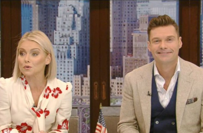 Screenshot from Live With Kelly and Ryan. Kelly Ripa on the left, Ryan Seacrest on the left, sitting at the desk.