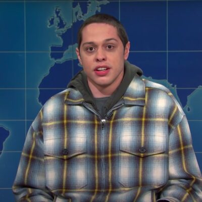 screenshot of Pete Davidson in a plaid jacket and hoodie on Saturday Night Live
