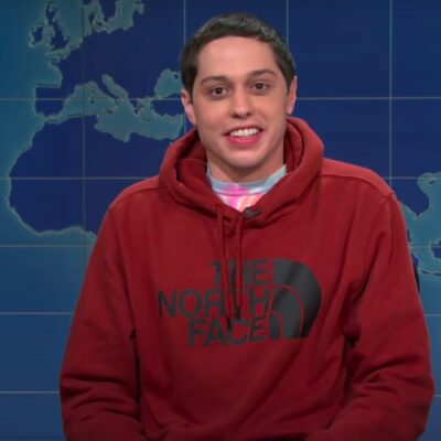 screenshot of Pete Davidson on Weekend Update on SNL with a red hoodie on