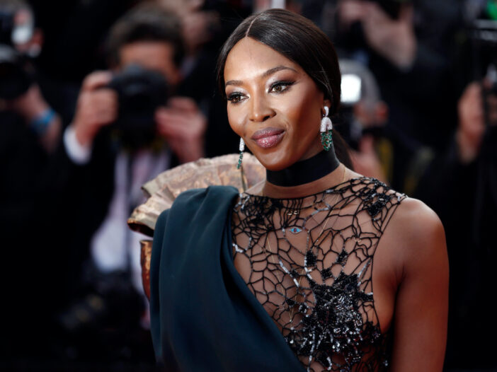Naomi Campbell smiling in a sheer black dress
