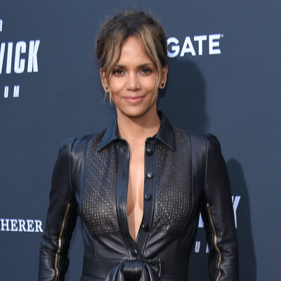 Halle Berry smiling in a black leather jumpsuit
