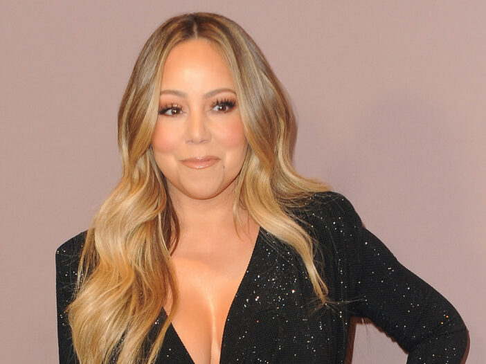 Mariah Carey smiling in a black dress