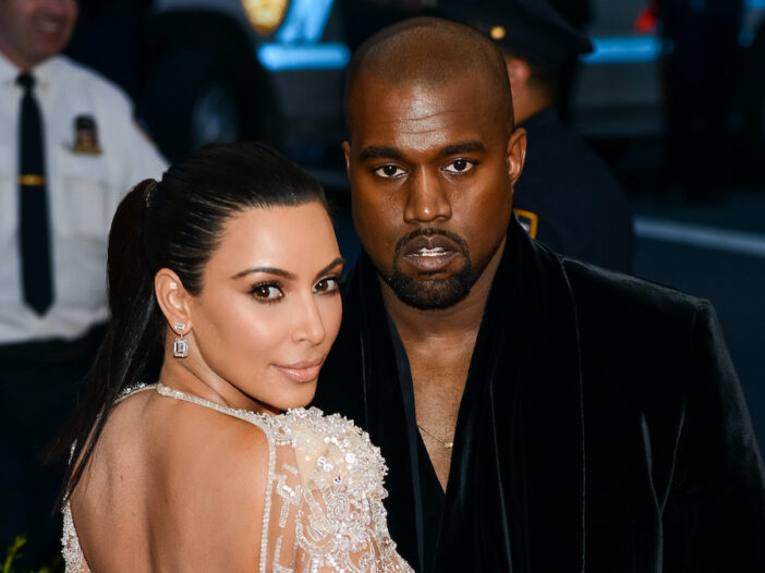 Kim Kardashian smiling with Kanye West frowning