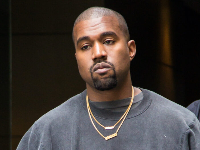 Kanye West frowning in a black sweatshirt and gold chain