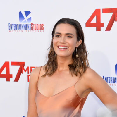 Mandy Moore smiling in a peach-colored dress.