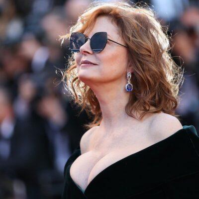 Susan Sarandon smiles in sunglasses and a black dress