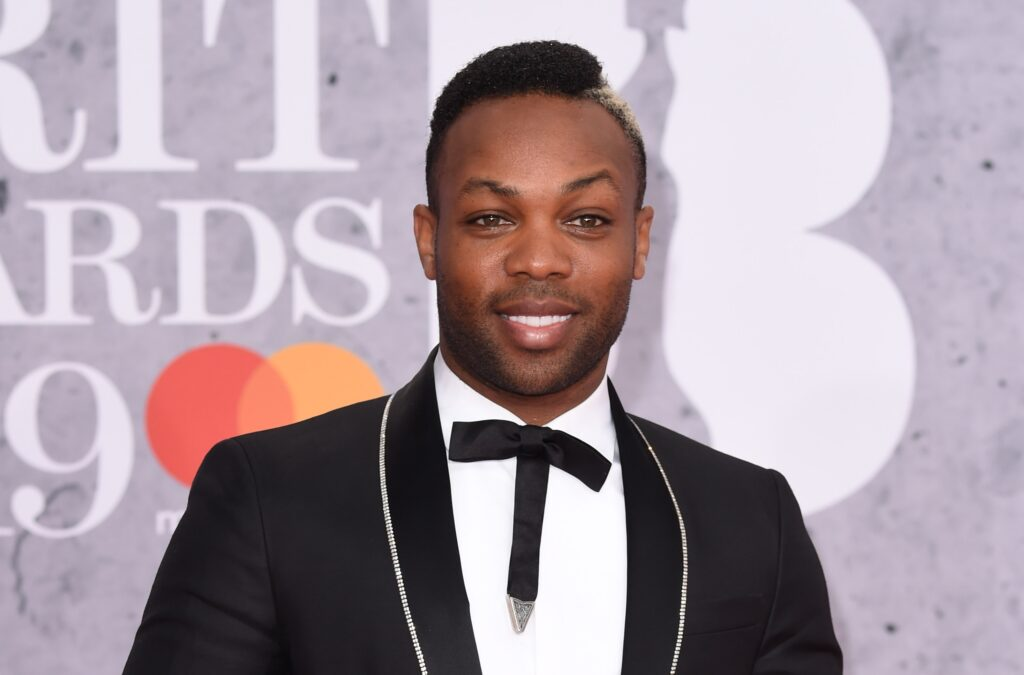 Todrick Hall in a black tux with a rhinestone trimmed lapel and skinny t-shaped tie at the BRIT Awards.