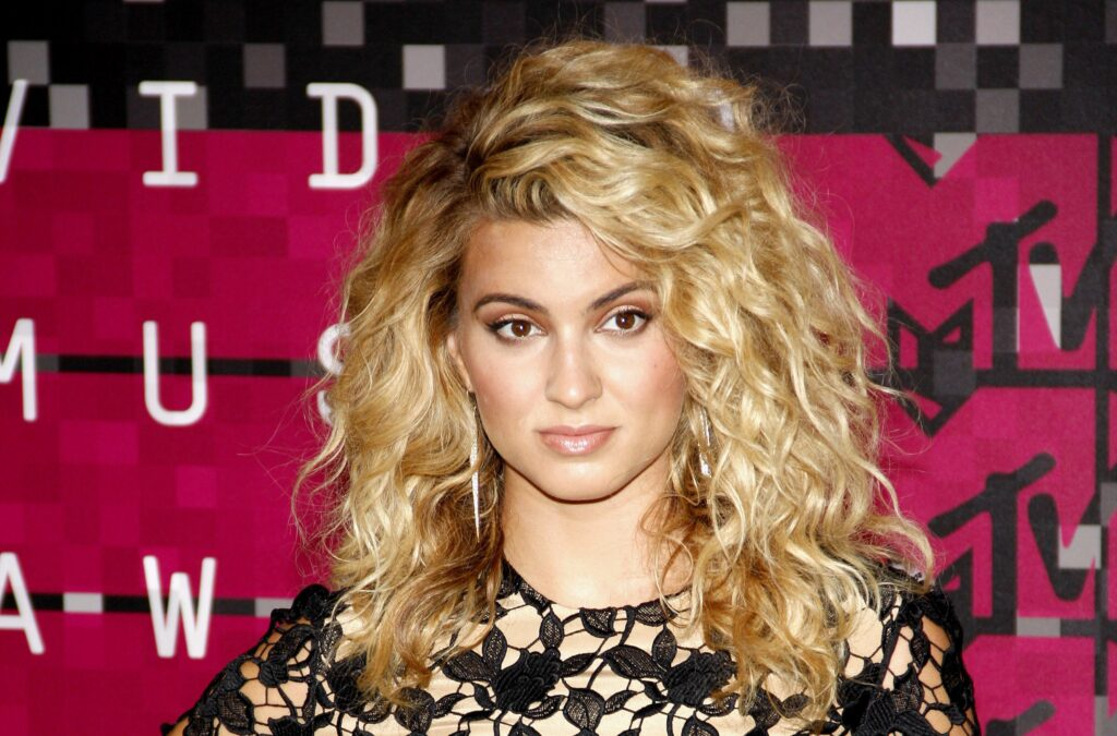 Tori Kelly in a black and tan lacy top rocking her signature wavy hair at the MTV Video Music Awards.